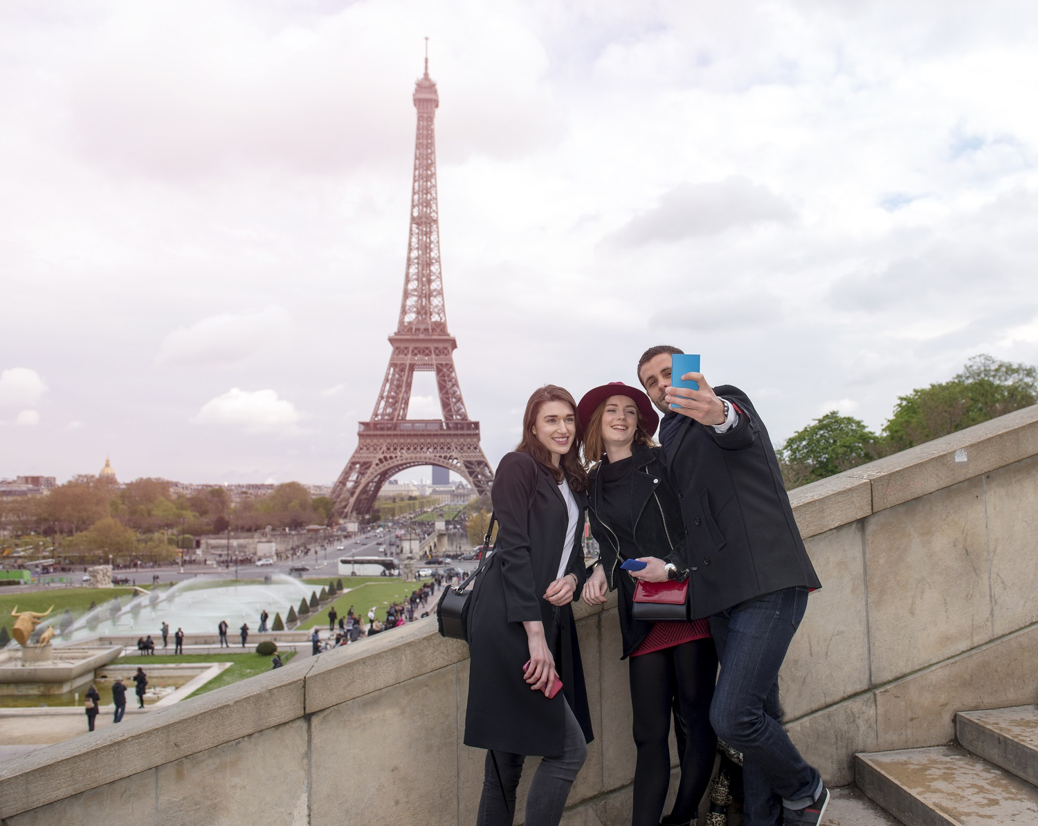 Portrait of friends using smartphone to take self portrait near the Eiffel Tower.
